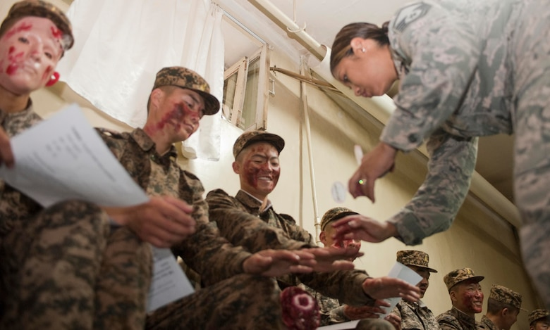 Master Sgt. Victoria Grey, enlisted medical subject-matter expert instructor, moulages members of the Mongolian armed forces as part of mass casualty response training during Operation Pacific Angel 14-4 Mongolia, Aug. 8, 2014, in Ulaanbaatar, Mongolia. Operation PACANGEL helped cultivate common bonds and fosters goodwill between the U.S., Mongolia and regional nations by conducting multilateral humanitarian assistance and civil military operations. (U.S. Air Force photo/Staff Sgt. William Banton)