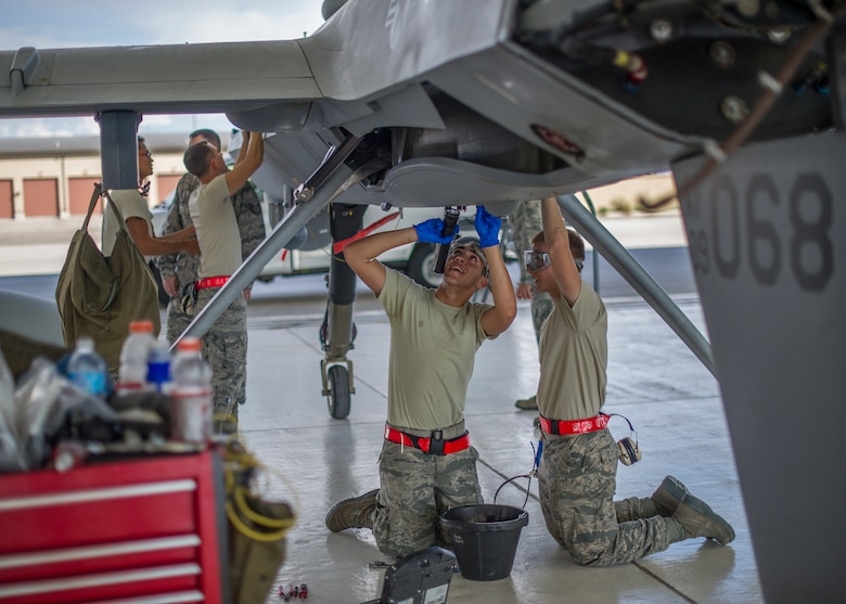 MQ-9 Reaper crew chiefs perform a routine inspection on an MQ-9 remotely piloted aircraft Aug. 12, 2014, at Holloman Air Force Base, N.M. The 49th Aircraft Maintenance Squadron thoroughly inspects each part of the aircraft before takeoff and after landing, looking for any discrepancies that could interfere with the proper operation of the aircraft. Additional inspections are completed on several milestones including 200, 400, 800 and 2,000 hours of flight time. Each inspection is more in-depth as the flight hours increase. The crew chiefs are assigned to the 49th AMXS. (U.S. Air Force photo/Airman 1st Class Leah Ferrante)