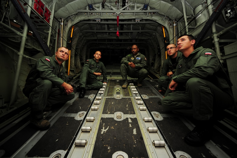Master Sgt. Chris Minnifield, center right, discusses the finer points of C-130 Hercules mass container delivery airdrop operations with Polish air force service members Aug. 11, 2014, at Powidz Air Base, Poland. The bilateral training was to prepare Polish forces to conduct equipment and supply delivery missions to Iraq. Minnifield is a 37th Airlift Squadron loadmaster. (U.S. Air Force photo/Staff Sgt. Jarad A. Denton)