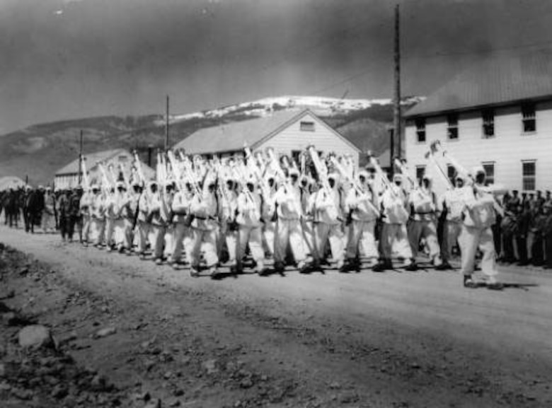 "10th Mountain Division soldiers parade down a street at Camp Hale, Colo., probably in 1943. They are wearing their ""whites"" the winter camouflage uniforms and carry white skis on their right shoulder as rifles are normally carried while on parade. Photo part of the Western History Collection at the Denver Public Library."