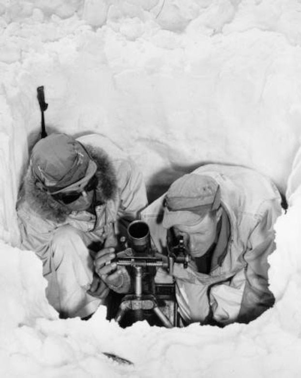 PFC Thomas Boulson and PFC Howard McDowell, huddle in a hole in the snow as McDowell sights a 60 mm mortar. The men fired practice rounds while on maneuvers at Resolution Mountain in Eagle County, Colo., in April 1944. Photo part of the Western History Collection at the Denver Public Library.