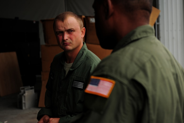 Polish Air Force Sierż (Sgt.) Zbigniew Krajniak, 33rd Transportation Air Base loadmaster, discusses mass container delivery airdrop operations with U.S. Air Force Master Sgt. Chris Minnifield, 37th Airlift Squadron loadmaster, at Powidz Air Base, Poland, Aug. 11, 2014. The discussion served as refresher training for Polish forces preparing to deliver equipment and supplies to Iraq. (U.S. Air Force photo by Staff Sgt. Jarad A. Denton/Released)