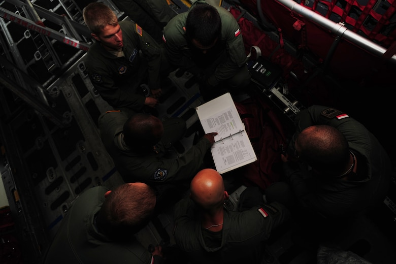 U.S. Air Force Master Sgt. Chris Minnifield, 37th Airlift Squadron loadmaster, center, reviews C-130E Hercules technical manuals with Polish Air Force C-130 loadmasters at Powidz Air Base, Poland, Aug. 11, 2014. Polish and American Service members came together to discuss operational tactics surrounding mass container delivery airdrop operations. (U.S. Air Force photo by Staff Sgt. Jarad A. Denton/Released)