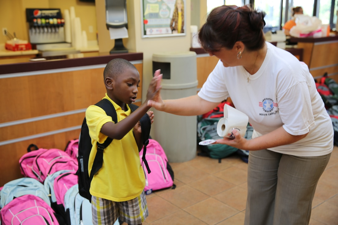 Jamie Rhodes, right, high-fives Khalil S. after handing him a backpack during Operation Homefront-Carolinas Back to School Brigade at Marine Corps Air Station Cherry Point, N.C., Aug. 15, 2014. School age children in grades ranging from pre-kindergarten to 12th grade received backpacks at the event. Rhodes is the family readiness officer with Marine Tactical Air Command Squadron 28. Khalil is a military dependent at Cherry Point.