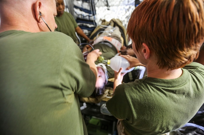 Sailors with 1st Medical Battalion, 1st Marine Expeditionary Brigade, notionally asses a patient for care as part of a simulated casualty evacuation at Marine Corps Air Ground Combat Center Twentynine Palms, Calif., Aug. 6, 2014. The casualty evacuation was part of Large Scale Exercise 2014, being conducted from Aug. 8-14. LSE-14 is a bilateral training exercise between the U.S. and Canada which includes live, simulated, and constructive operations to enhance both countries' ability to activate and deploy a Marine Air Ground Task Force with speed and effectiveness in support of the full range of military operations as required by combatant commanders. (U.S. Marine Corps photo by Lance Cpl. Caitlin Bevel)