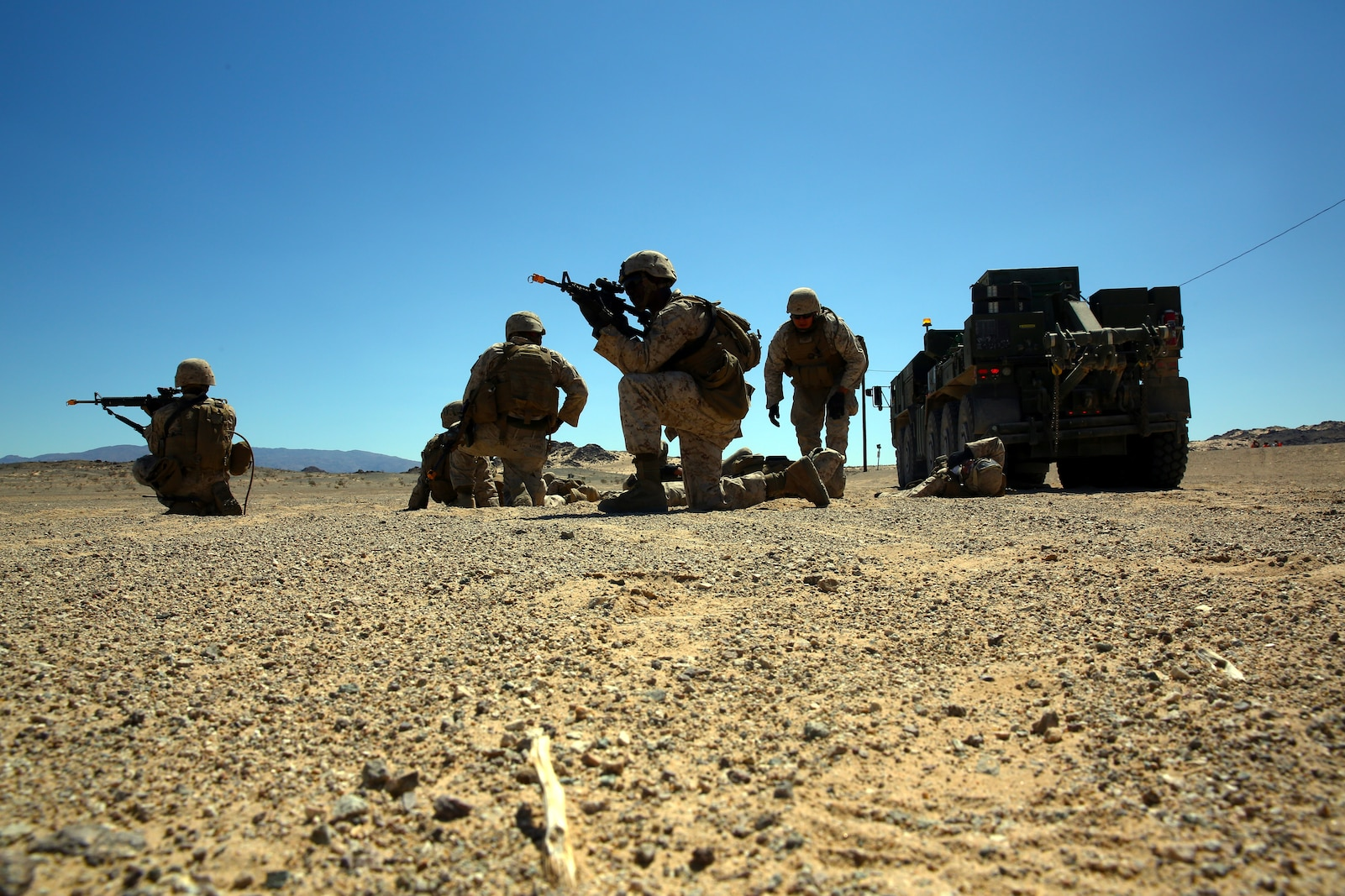 Marines with Combat Logistics Battalion 5, Combat Logistic Regiment 1, 1st Marine Logistics group, I Marine Expeditionary Force, set up a casualty evacuation sight as a hospital corpsmen evaluates the simulated wounded during exercise Backlog aboard Marine Air Ground Combat Center, Twentynine Palms, Calif., August 7, 2014. This exercise was the cumulating event of a 30-day integrated training exercise in which Marines were instructed in multiple types of convoys and standard operating procedures for unfamiliar scenarios. (Official Marine Corps Photo by Lance Corporal Ashton Buckingham)
