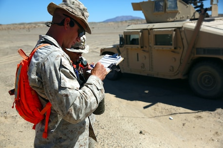 A Marine evaluator attached to Combat Logistics Battalion 5, Combat Logistic Regiment 1, 1st Marine Logistics group, I Marine Expeditionary Force, grades a squad of Marines during exercise Backlog aboard Marine Air Ground Combat Center, Twentynine Palms, Calif., August 7, 2014. This exercise was the cumulating event of a 30-day integrated training exercise in which Marines were instructed in multiple types of convoys and standard operating procedures for unfamiliar scenarios. (Official Marine Corps Photo by Lance Corporal Ashton Buckingham)