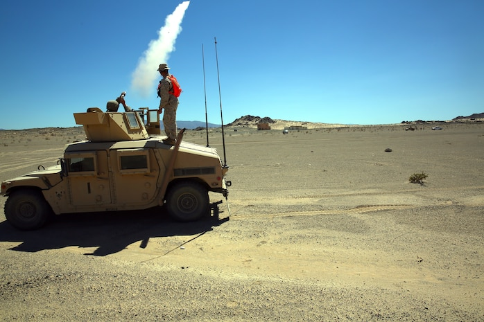A Marine with Combat Logistics Battalion 5, follows the standard operation procedure to warn an incoming truck to not proceed any closer, during exercise Backlog aboard Marine Air Ground Combat Center, Twentynine Palms, Calif., August 7, 2014. This exercise was the cumulating event of a 30-day integrated training exercise in which Marines were instructed in multiple types of convoys and standard operating procedures for unfamiliar scenarios. (Official Marine Corps Photo by Lance Corporal Ashton Buckingham)