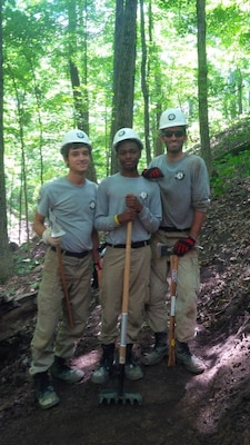 Members of Maple 1 take a break on Chief Illini Trail along Lake Shelbyville in central Illinois. Darius, center, is holding a rake-hoe tool called a Mccleod, while Steven and Vincent are holding pick-axe type tools called a Pulaski.