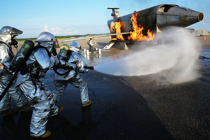 Aircraft Rescue and Firefighting Marines approach a simulated aircraft crash at Marine Corps Air Station Cherry Point, N.C., Aug. 14, 2014. The Marines honed their firefighting skills by dealing with the stressors and procedures of aircraft fires first hand.
