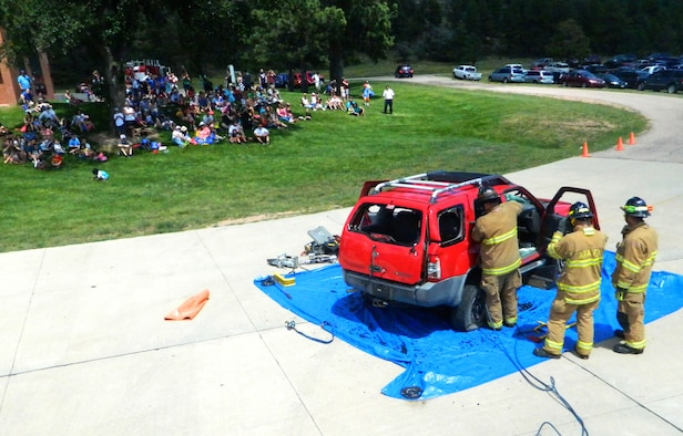 Firefighters from the 10th Civil Engineer Squadron fire department provide  a vehicle extrication demonstration during an open house Aug. 16. (U.S. Air Force photo/Mike Mater)