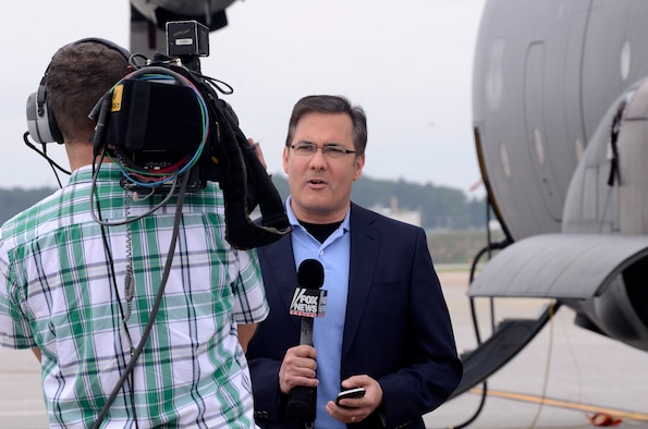 Jonathan Serrie, Fox News Channel correspondent, broadcasts live from the Dobbins Air Reserve Base airfield Aug. 19, 2014 in recognition of the 60th Anniversary of the C-130 aircraft. (U.S. Air Force photo/Don Peek)