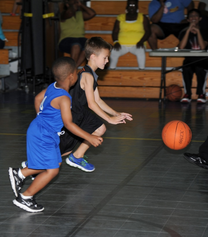 The son of Senior Master Sgt.  Jason Holbert, 81st Communications Squadron, drives the ball down the court as the son of Senior Airman Michael Mitchell, 916th CS, Seymour Johnson Air Force Base, N.C., defends during a youth basketball game Aug. 16, 2014, at the Youth Center, Keesler Air Force Base, Miss.  This was a friendly game between the 76ers and the Knicks five-to-seven year old teams. (U.S. Air Force photo by Kemberly Groue)