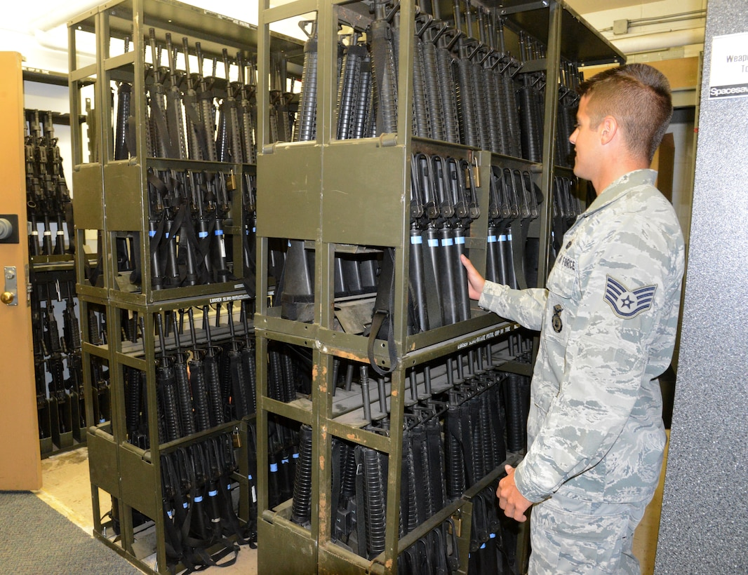 Staff Sgt. Michael Enerud retrieves a weapon from a new section of inventory in the Security Forces armory. He, along with the other SFS members who work there, took the initiative to reorganize the area to make it more efficient for SFS members needing to check in/out weapons and ammunition for their shifts. The 'Just Do It' initiative will save the government more than $373,000 a year. 