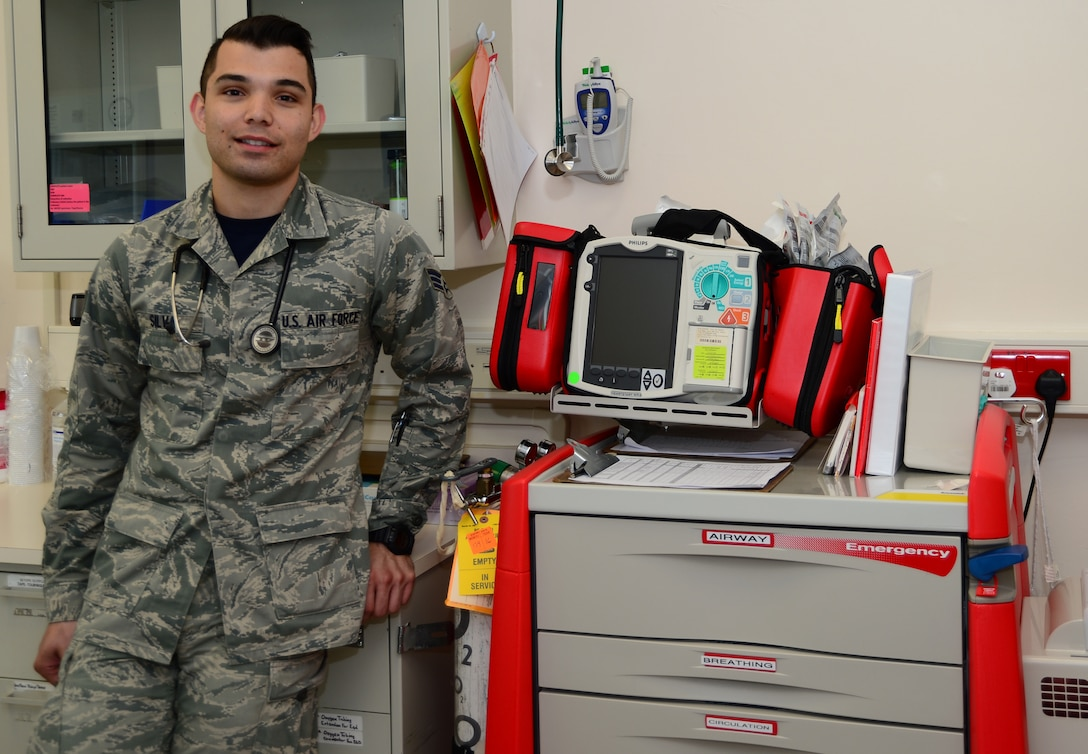 U.S. Air Force Senior Airman Christian Silva, an aerospace medical technician, stands in his clinic workplace Aug. 15, 2014, at Royal Air Force Lakenheath, England. Silva was instrumental in saving the life of a U.S. Navy Sailor who collapsed while working out at Misawa Air Base's fitness center. Silva applied multiple Automated External Defibrillator shocks and CPR before transporting the patient to the hospital for emergency surgery. (U.S. Air Force photo/Airman 1st Class Dana Butler)