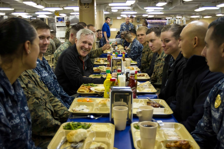 "Secretary of the Navy Ray Mabus eats dinner with Marines and Sailors with Special Purpose Marine Air Ground Task Force South and the future amphibious assault ship USS America (LHA 6) in the mess deck aboard the ship, Aug. 19, 2014. The dinner with the Marines and Sailors allowed for topics of interest to be discussed on a personal level. In addition to dinner, Mabus toured the ship, held an all-hands call to address the crew and attended an ice cream social. Visits like this remind the Marines and Sailors with America and the SPMAGTF of the significance of the work they are doing. SPMAGTF-South is embarked aboard America in support of her maiden transit, ""America Visits the Americas."" Through partner-nation activities, theater security events and key leader engagements, the transit aims to demonstrate the flexibility, utility and unparalleled expeditionary capability the Navy-Marine Corps team provides our nation and partners. (U.S. Marine Corps Photo by Cpl. Donald Holbert/ Released)"
