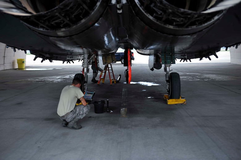 Airman 1st Class Blake Destasio looks at a technical order prior to checking the engine oil on an F-15 Strike Eagle in a hangar Aug. 14, 2014, on Osan Air Base, South Korea. Technical orders, loaded on rugged laptops, are used to facilitate maintenance on aircraft by providing Airmen with reference material. Destasio is a 391st Aircraft Maintenance Unit crew chief (U.S. Air Force photo/Senior Airman David Owsianka)