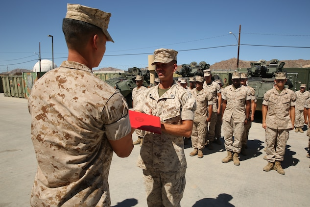 Capt. Kelvin Chew, communications officer, S-6, 3rd Light Armored Reconnaissance Battalion, hands Sgt. Arthur E. Krenzel III, field radio operator, 3rd LAR, his promotion warrant during his meritorious promotion ceremony at the Communications Building of 3rd LAR, Aug. 15, 2014.