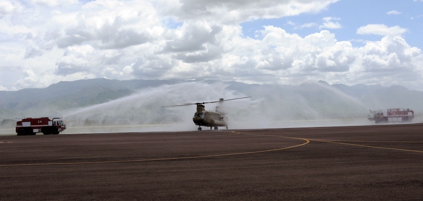 """A new CH-47F Chinook helicopter receives a """"bird bath"""" from the Soto Cano Air Base Fire Department June 21, 2014, after landing in Honduras for the first time.  The 1-228th Aviation Regiment transitioned to the new air frame from the CH-47D after being the last active duty unit in the Army to fly the historic behemoths, which began their service during the 1960's.   (Photo by U. S. Air National Guard Capt. Steven Stubbs)"""