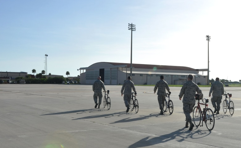 Members from the 920th Maintenance Squadron walk their bikes on the flightline, Patrick Air Force Base, Fla., August 19, 2014. The members are part of a cycling club and plan to participate in the Rocketman Florida Triathlon, October 12, 1014. (U.S. Air Force photo/ Tech. Sgt. Katie Spencer)