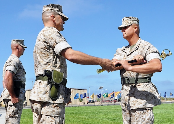 Col. Benjamin Stinson, MCTSSA commanding officer, passes a ceremonial sword to MCTSSA's new sergeant major, Brandon Hall, symbolizing the transfer of duties from outgoing Sgt. Maj. Kenneth Warren during the activity's relief and appointment ceremony Aug. 14 at Camp Pendleton, California. The sword, as the oldest form of weapon still in use, has come to symbolize material leadership.