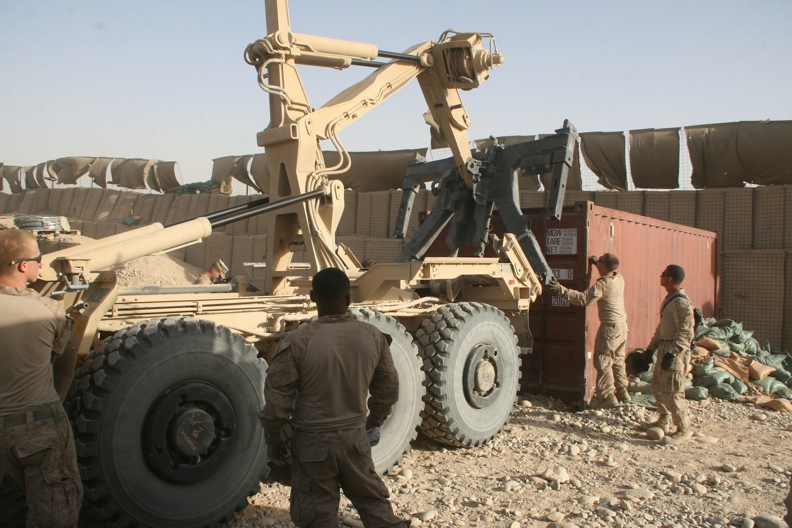 Marines with Combat Logistics Battalion 1, Regional Command (Southwest), assist a logistics vehicle system replacement operator during a retrograde operation aboard Patrol Base Boldak, Helmand province, Afghanistan, Aug. 14, 2014. The operation was designed to retrograde the majority of the excess gear and equipment such as living quarters containers and air conditioning units from PB Boldak.