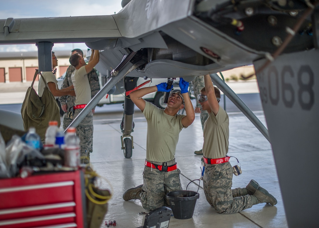MQ-9 Reaper crew chiefs perform a routine inspection Aug. 12, 2014, on an MQ-9 remotely piloted aircraft at Holloman Air Force Base, N.M. The 49th Aircraft Maintenance Squadron thoroughly inspects each part of the aircraft before takeoff and after landing, looking for any discrepancies that could interfere with the proper operation of the aircraft. Inspections are performed based on various factors including total hours flown and discrepancies noticed or reported during training sorties. The crew chiefs are assigned to the 49th AMXS. (U.S. Air Force photo/Airman 1st Class Leah Ferrante)