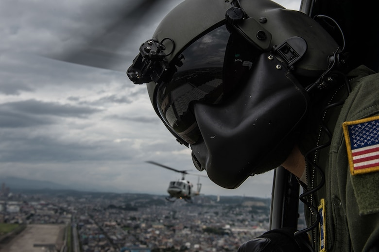 Staff Sgt. Michael Wright scans the area for potential obstacles during a training mission Aug. 12, 2014, near Yokota Air Base, Japan. Wright is a 459th Airlift Squadron UH-1N Huey helicopter crew chief. (U.S. Air Force photo/Staff Sgt. Stephany Richards)