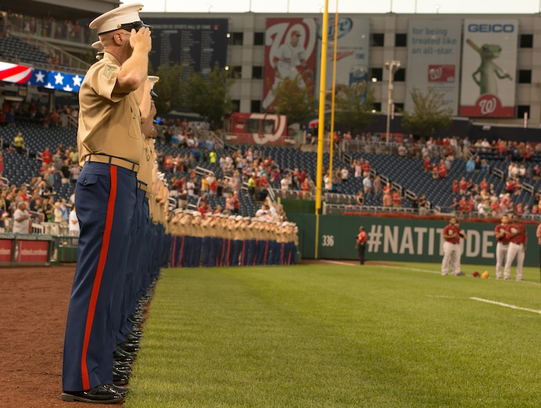 Marines salute the flag during the national anthem at the Washington Nationals game against the Arizona Diamond backs at Nationals Park on August 20, 2014. General James Amos, the commandant of the Marine Corps, threw the first pitch of the game.