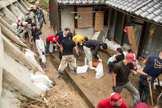 Marines from Marine Corps Air Station Iwakuni, Japan, and Japanese locals clean up damage done by Typhoon Halong behind a residence in Sunayamacho, Iwakuni, August 14, 2014. More than 30 service members volunteered to help out the local community clean up the typhoon damage.