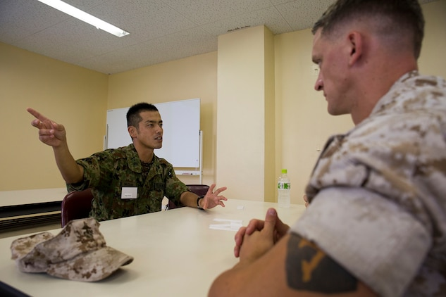Master Sgt. Hideyuki Watabe, an infantryman with the Japanese Ground Self-Defense Force's 13th Brigade, 46th Regiment, left, explains aspects of JGSDF training to Sgt. Giancarlo Maragni, a Corporals Couse instructor from Marine Corps Air Station Iwakuni, Japan, during an English seminar aboard JGSDF Base Kaita in Hiroshima, August 8, 2014. The purpose behind the tour was to provide Marines the opportunity to visit and experience the Japanese military lifestyle and training requisites.