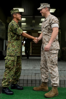 Master Sgt. Hideyuki Watabe, an infantryman with the Japan Ground Self-Defense Force's 13th Brigade, 46th Regiment, left, and Lance Cpl. Thomas Breiter, a patrolman with the Provost Marshal's Office aboard Marine Corps Air Station Iwakuni, Japan, shake hands at the end of an English seminar aboard JGSDF Base Kaita in Hiroshima, August 8, 2014. The purpose behind the tour was to provide Marines the opportunity to visit and experience the Japanese military lifestyle and training requisites.