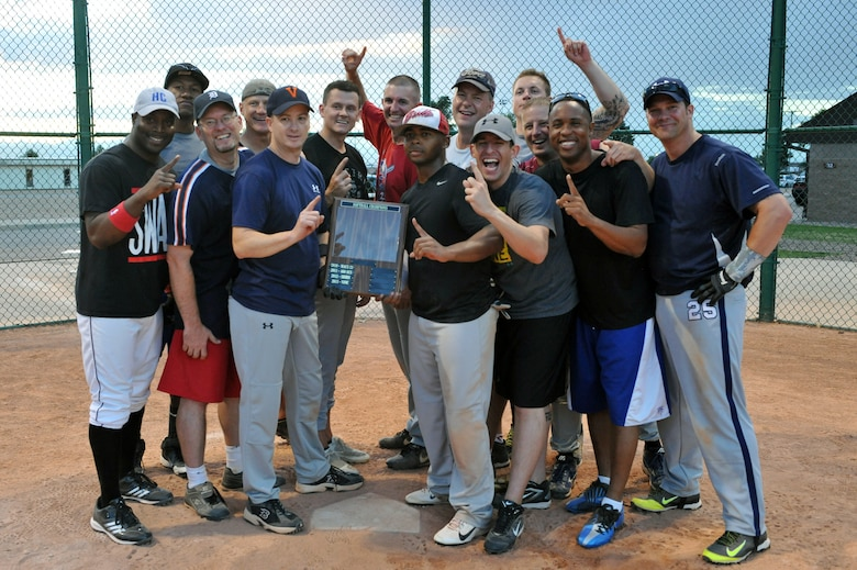The 460th Space Wing Staff softball team poses for a celebratory photo at home plate after the championship softball game Aug. 20, 2014 at the softball fields on Buckley Air Force Base, Colo. The final score of the game was 24-9, making the wing staff team the 2014 intramural softball base champions. (U.S. Air Force photo by Airman Emily E. Amyotte/Released)