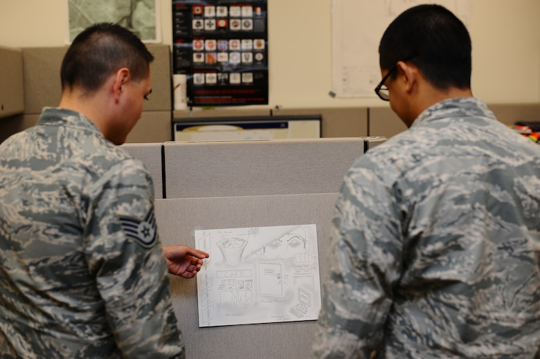 Airmen from the 460th Space Wing Plans and Programs office view the winning poster from the Operations Security poster contest on Buckley. The poster, submitted by Staff Sgt. Ashley Glasgow, 460th Security Forces Squadron supervisor, will go on to compete with other posters at Air Force Space Command. (U.S. Air Force photo by Senior Airman Darren Scott/Released)