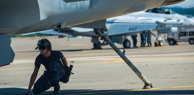 A Navy EA-18G Growler maintainer completes a check before take-off Aug. 6, 2014, at Naval Air Station Whidbey Island, Wash. The Navy and Air Force have the added benefit of understanding Navy terms and are able to translate to their Air Force partners. (U.S. Air Force photo by Airman 1st Class Malissa Lott)