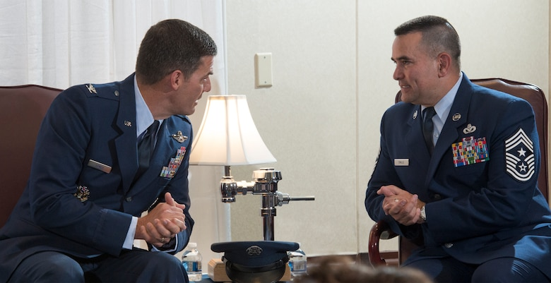 Col. Dwight Sones, left, former 60th Air Mobility Wing commander, and retired Chief Master Sgt. John Evalle, former 60th AMW command chief, talk Aug. 15 at Evalle's retirement ceremony. Sones presided over the ceremony. (U.S. Air Force photo by Heide Couch)