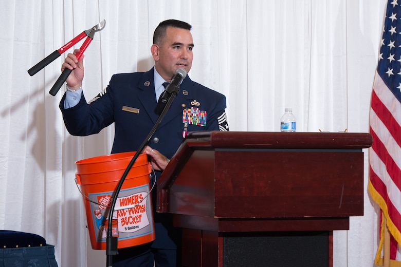 Evalle holds hedge clippers and a bucket during his parting remarks. (U.S. Air Force photo by Ken Wright)