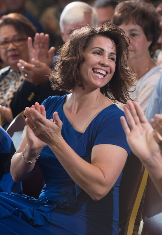 Retired Chief Master Sgt. John Evalle's wife applauds Aug. 15 during her husband's retirement ceremony. (U.S. Air Force photo by Ken Wright)