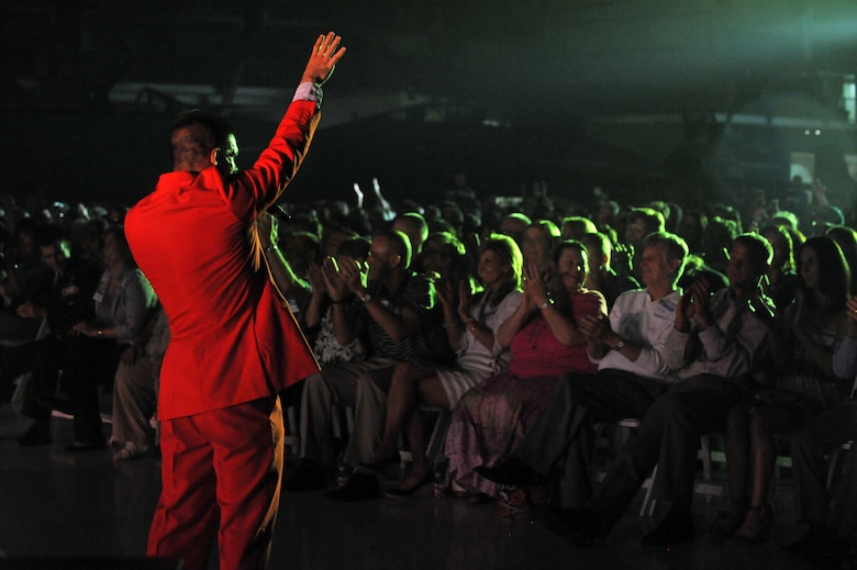 A U.S. Air Force's Tops in Blue member sings to the crowd during a performance Aug. 19, 2014, at the Wings Over the Rockies Air and Space Museum in Denver.  Tops in Blue is the Air Force's premier entertainment showcase that tours around the world, performing in 20 countries and more than 70 locations in the United States each year. (U.S. Air Force photo by Airman Emily E. Amyotte/Released)