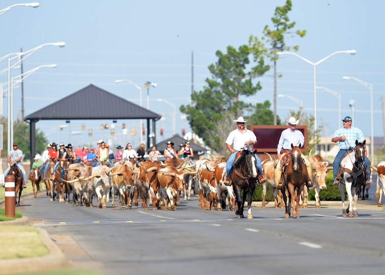 ALTUS AIR FORCE BASE, Okla. – Ranchers from the Great Plains Stampede Rodeo guide a herd of longhorn cattle onto Altus AFB during the 16th Annual Base Cattle Drive, Aug. 21, 2014. The event is a tradition that started Aug. 26, 1999 when 15 riders drove a herd of longhorn cattle through the streets of Altus AFB. (U.S. Air Force photo by Senior Airman Levin Boland/Released)