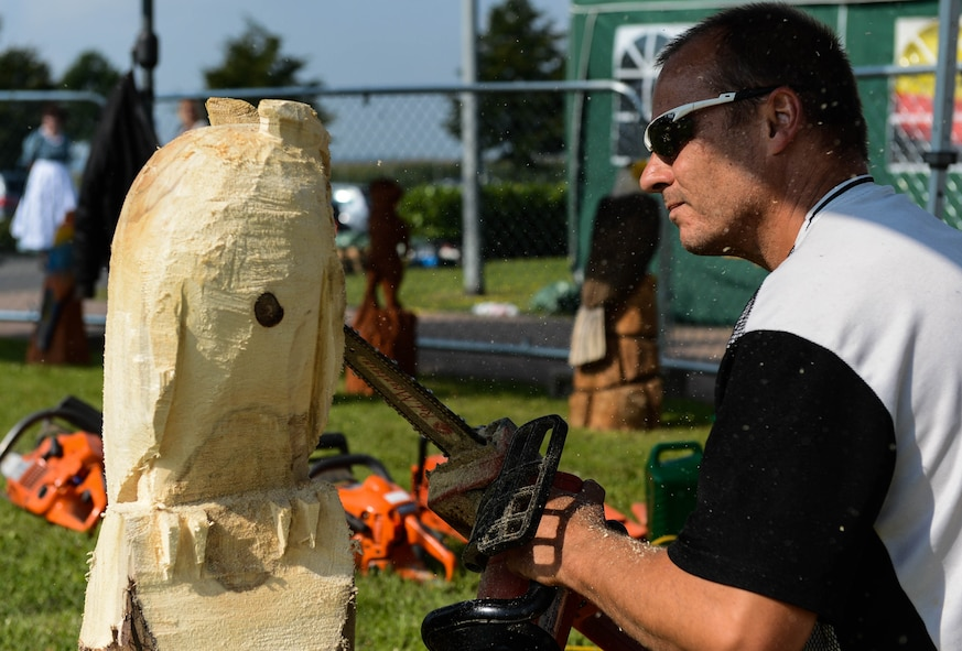 Dietmar Schier, a sculptor from Landscheid, Germany, uses a chainsaw to sculpt an owl during a Diversity Day celebration at Spangdahlem Air Base, Germany, Aug. 21, 2014. Event coordinators host Diversity Day each year to recognize the importance of mutual respect for others. (U.S. Air Force photo by Airman 1st Class Kyle Gese/Released)