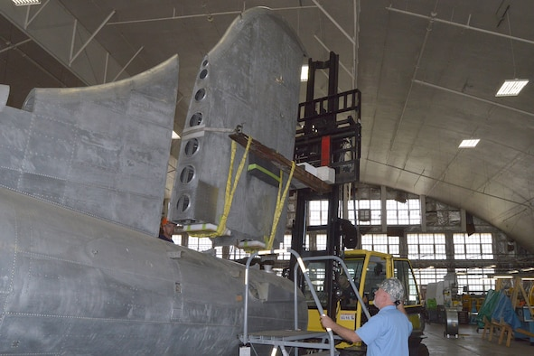 """DAYTON, Ohio (08/2014) -- (From left to right) Restoration Specialists Duane Jones, Chad Vanhook, and Roger Brigner attach the vertical stabilizer to the fuselage of the B-17F """"Memphis Belle""""® at the museum's restoration hangar. Plans call for the aircraft to be placed on display in the museum's World War II Gallery in spring 2018. (U.S. Air Force photo)"""