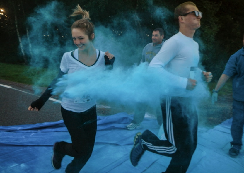 Participants are showered in color Aug. 21, 2014, during the Diversity Day 5K Color Run at Spangdahlem Air Base, Germany. Volunteers threw colored powder at participants at designated points on the route. (U.S. Air Force photo by Staff Sgt. Christopher Ruano/Released)