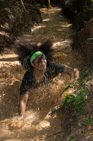 A mud run participant tumbles into the mud during the second annual Tier II 5K Mud Run Aug. 20, 2014, at Spangdahlem Air Base, Germany. More than 100 people participated in the mud run. Private organizations from around the base worked together to build the obstacles for runners. (U.S. Air Force photo by Staff Sgt. Christopher Ruano/Released)