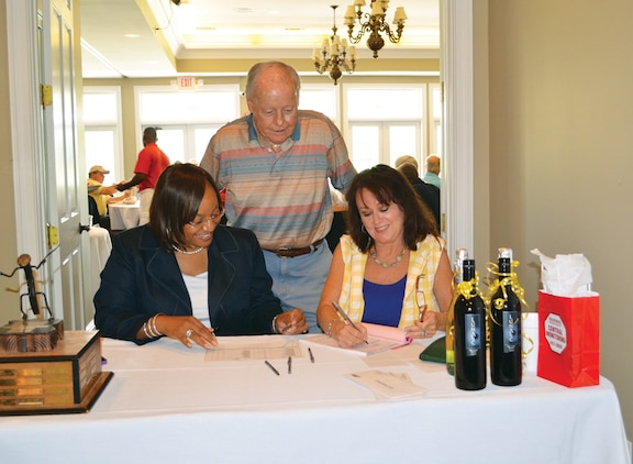 Pamela Jackson, (left) community plans and liaison officer, Marine Corps Logistics Base Albany, checks in participants for the Salty Sandbagger Golf Tournament at River Pointe Golf Club, June 4, while Leland Burkart, chairman, Military Affairs Committee, (standing) and Sue Corbin, marketing and events coordinator, Albany Area Chamber of Commerce, assist.