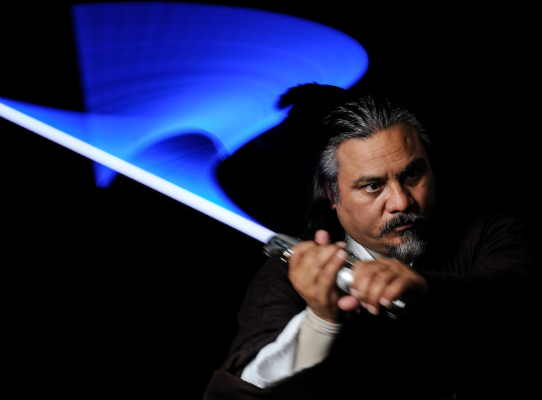 Randy Sena  wields his lightsaber while dressed in a Jedi costume he made himself. An avid cosplayer, Sena has won several awards for his designs. Sena is the 11th Wing chief of exercises at Joint Base Andrews, Md. (U.S. Air Force photo/Staff Sgt. Rob Cloys)