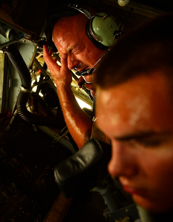 Tech Sgt. Ryan Riley wipes sweat from his brow while he and Airman 1st Class Connor Sweeney work together to adjust the aircrafts boom pod shaft Aug. 5, 2014, at Al Udeid Air Base, Qatar. Airmen who perform maintenance on the flightline here endure stifling heat, sand and wind to keep air refueling aircraft and a multitude of other airframes taking off and landing day and night. Sweeney is a 340th Expeditionary Aircraft Maintenance Unit hydraulic systems craftsmen. (U.S. Air Force photo/Staff Sgt. Vernon Young Jr.)