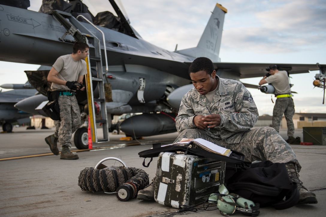 Airman Ezra Jones checks flight forms during Red Flag-Alaska 14-3 Aug. 19, 2014, on Eielson Air Force Base, Alaska. RF-A is a two week-long exercise that gives participants the opportunity to train in large-scale combat simulations involving aircraft from allied and coalition forces from around the world. Jones is a 80th Aircraft Maintenance Squadron aviation systems specialist assigned to Kunsan Air Base, South Korea. (U.S. Air Force photo/Senior Airman Peter Reft)