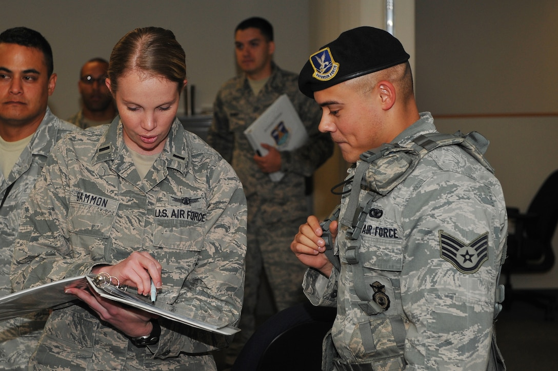 1st Lt. Ashley Gammon, 2nd Space Warning Squadron, left, reviews the building evacuation plan with Staff Sgt. Vincent Rios, 460th Security Forces Squadron, after a simulated bomb scenario during the Panther Challenge Aug. 11, 2014,on Buckley Air Force Base, Colo. The challenge, held Aug. 4-13, was developed to provide members of Team Buckley an opportunity to improve their skills and expand their job knowledge in a competitive setting. Participants in the challenge included the 2nd and 8th Space Warning Squadrons, 460th Security Forces Squadron, and 460th Medical Group. (U.S. Air Force photo by Senior Airman Phillip Houk/Released)