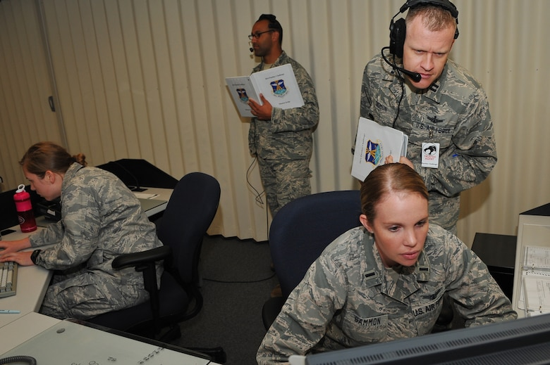 1st Lt. Ashley Gammon, 2nd Space Warning Squadron, seated right, works in the command section of the 460th Operations Group Panther Challenge while being evaluated by Capt. Rhett Sigmon, 460th OG, standing right, during the 460th OG Panther Challenge Aug. 11, 2014, on Buckley Air Force Base, Colo. The challenge, held Aug. 4-13, was developed to provide members of Team Buckley an opportunity to improve their skills and expand their job knowledge in a competitive setting. Participants in the challenge included the 2nd and 8th Space Warning Squadrons, 460th Security Forces Squadron, and 460th Medical Group. (U.S. Air Force photo by Senior Airman Phillip Houk/Released)